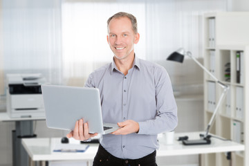 Confident Businessman Holding Laptop In Office