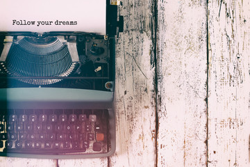 abstract vintage filtered image of top view photo of vintage typewriter with the phrase: follow your dreams, on wooden table. retro filtered image