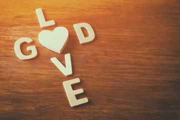 selective focus photo of The words love is god made with block wooden letters on wooden background. religion concept. vintage filtered and toned