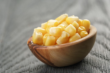 sweet canned corn in wood bowl on wood table