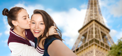 teenage girls taking selfie over eiffel tower