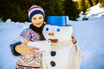 Snow and winter fun, happy girl takes a picture with snowman