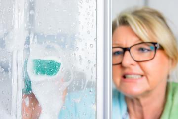 frau säubert die duschwand