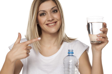 Smiling woman pointing to a full glass of water