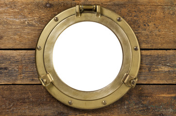 Vintage brass porthole in wooden wall isolated with clipping path