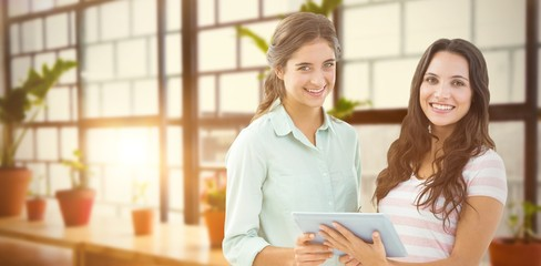 Composite image of smiling businesswoman with tablet
