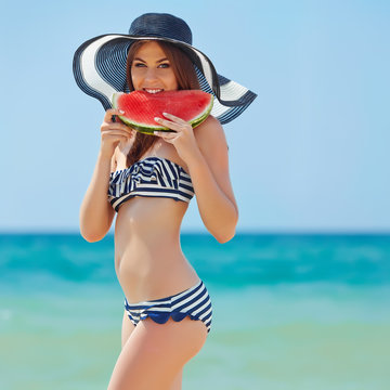 Beautiful woman on the beach with watermelon