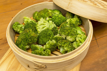 Close up of steamed broccoli in a bamboo pan.