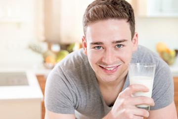 Junger Mann mit Glas frischer Milch zum Frühstück