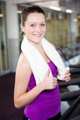 Smiling fit woman with towel around her neck
