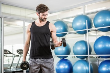 Concentrated man lifting dumbbells