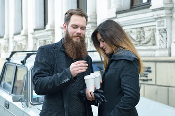 Autumn outdoor fashion portrait of young couple drinking coffee