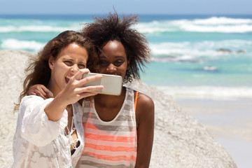Smiling young women taking selfie at the beach
