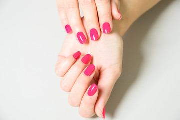 High Angle Close Up of Woman Applying Bright Pink Colored Nail Polish to Finger Nails Using Brush with Bottle Close By on White Surface with Copy Space