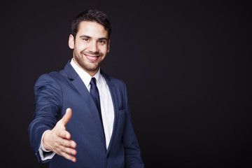 Businessman giving his hand for handshake on black background