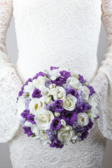 White and purple wedding bouquet of roses, freesias and lisianthus flowers
