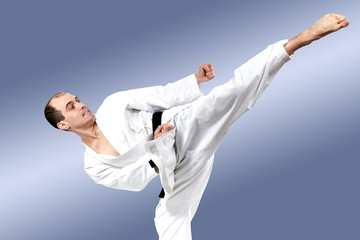 In karate gi sportsman beats roundhouse kick