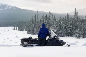 Woman on snowmobile in the mountains.