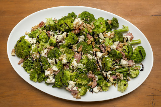Close up of fresh broccoli salad with bacon, feta cheese and walnuts drizzled with olive oil and good quality balsamic vinegar.