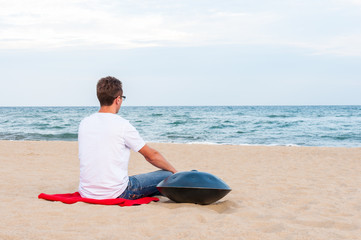 Young stylish guy sitting on the sand beach near handpan or hang with sea On Background. The Hang is traditional ethnic drum musical instrument