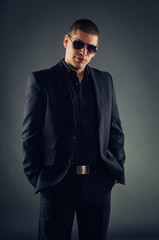 Handsome macho man in suit and sunglasses