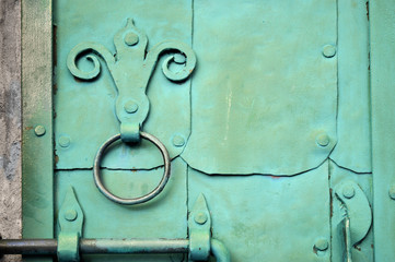 Old green door with rivets and aged metal door handle in the form of stylized lily. Textured industrial background.