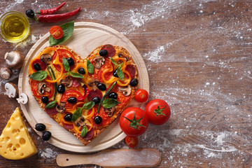 Tasty heart shaped pizza decorated with vegetables and herbs on wooden background. Happy Valentines day. love concept