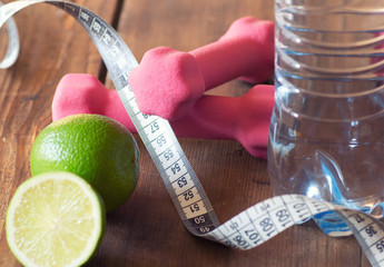 weight loss concept with tape measure organic lime, pink dumbbells and natural bottle of water