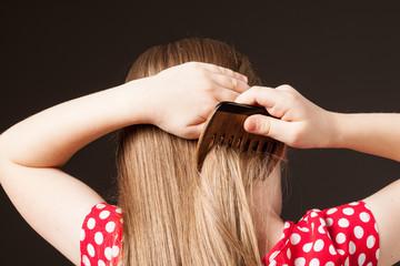 Little girl combing her beautiful long hair