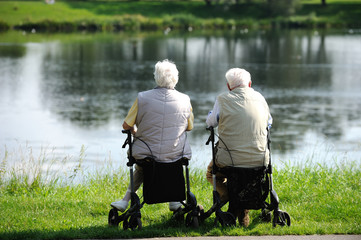 Zwei Rentner sitzen auf Rollatoren und sehen auf einen See.