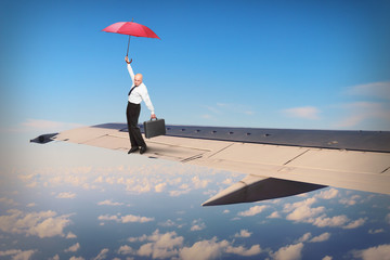Passenger or pilot with umbrella ballancing on airliner wing. Travel insurance concept. Funny situation from travel.