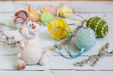 Easter bunny, pussy willow and handmade Happy Easter eggs on a light wooden background