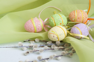 Pussy willow and handmade Happy Easter eggs on a light wooden background