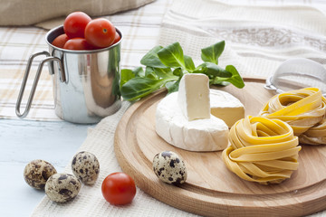 Raw homemade pasta, camembert, quail easter eggs in a aluminum cup, green lettuce, tomatoes and flour on wooden table