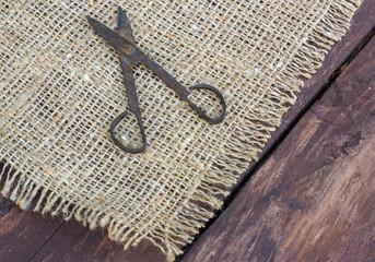 кованные старые ножницы ручной работы на фоне мешковины