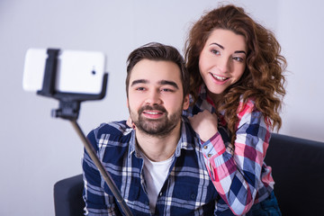 young beautiful couple taking photo with smart phone on selfie s