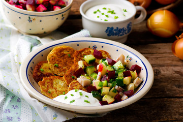 potato fritters with herring and vegetables