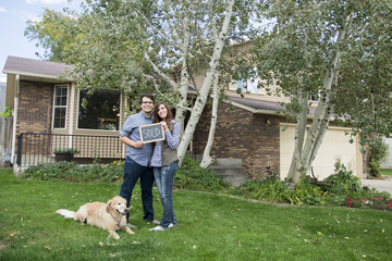 couple and dog in front of new home with sold sign