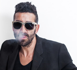 Handsome man portrait smoking cigarette and wearing sunglasses