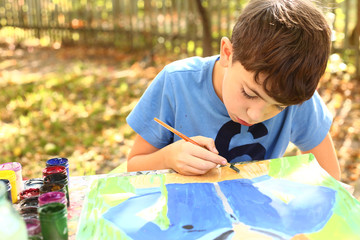preteen handsome boy painting with gouache