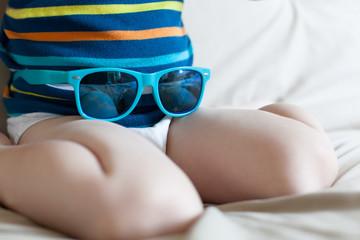 Closeup of boy having fun with sunglasses