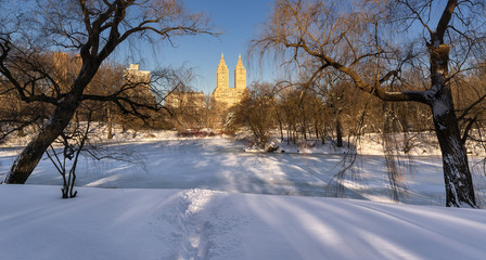 Winter sunrise on The Lake, frozen and covered in fresh snow, in Central Park, with view on Upper West Side buildings. Wintertime in Manhattan, New York City