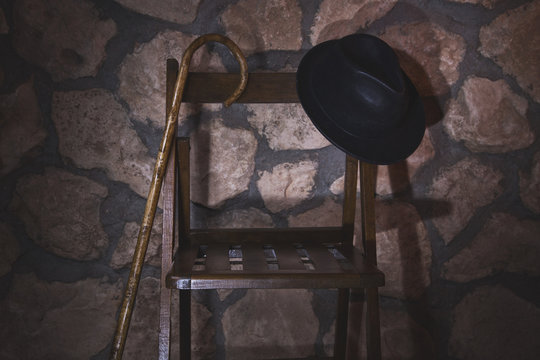 Old hat and cane on a chair