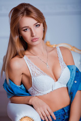 Sexy beautiful young woman posing on vintage chair. Girl in jeans and white bra.