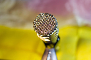 Silver microphone on blurred yellow background