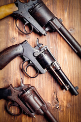 Vintage pistols on wooden background