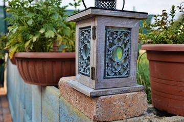 lantern on bricks wall at summertime, Garden lamp with two flowerpots,  vintage kerosene  lamp isolated on garden background,