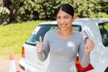 Fototapete - young woman showing a driving license