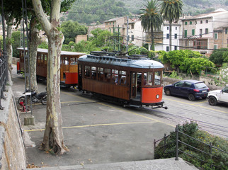 Vintage Tram runs through the  market square in Soller close to cafes and people. Majorca Spain.