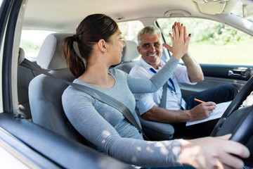 Fototapete - young learner driver and driving instructor high five